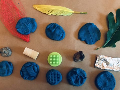 Eight mounds of blue playdough with varied indentations. Aabove each mound is the object used to create the indentation, including a feather, tin foil, leaf, and rock.