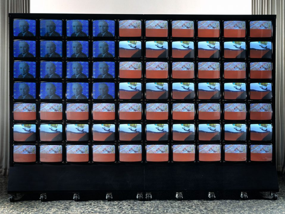 An arrangement of small television monitors stacked to collectively display one large American flag.