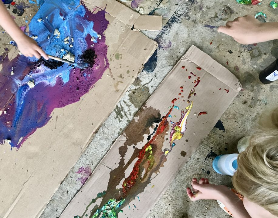 People leaning over two large pieces of cardboard, dripping and splashing paint onto the surface