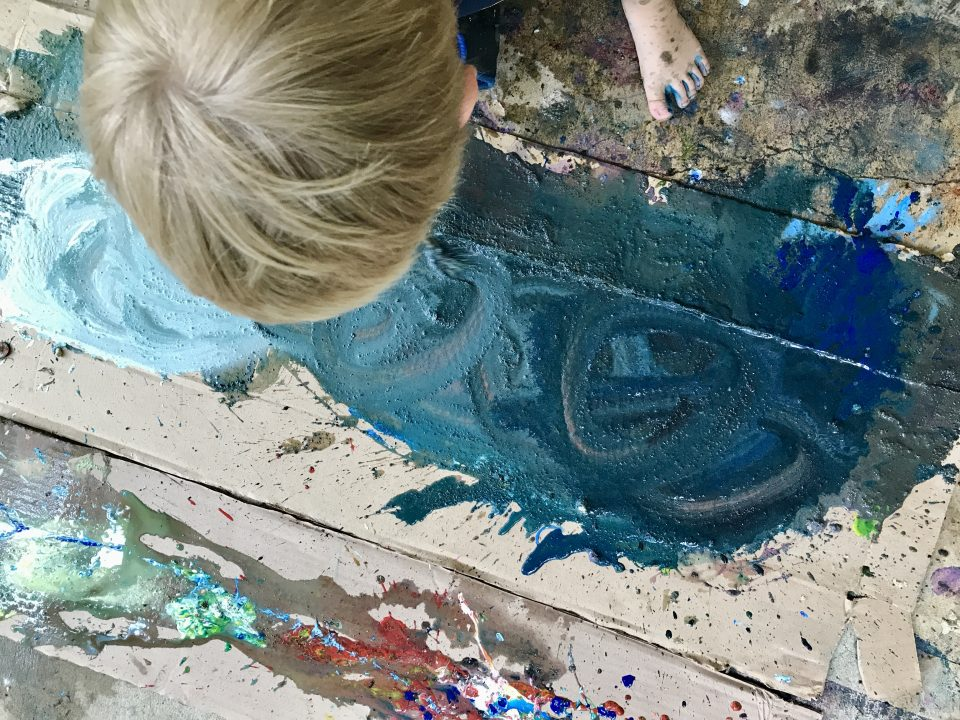 Overhead view of a child walking on a large piece of cardboard that is covered with splatters and smears of paint.