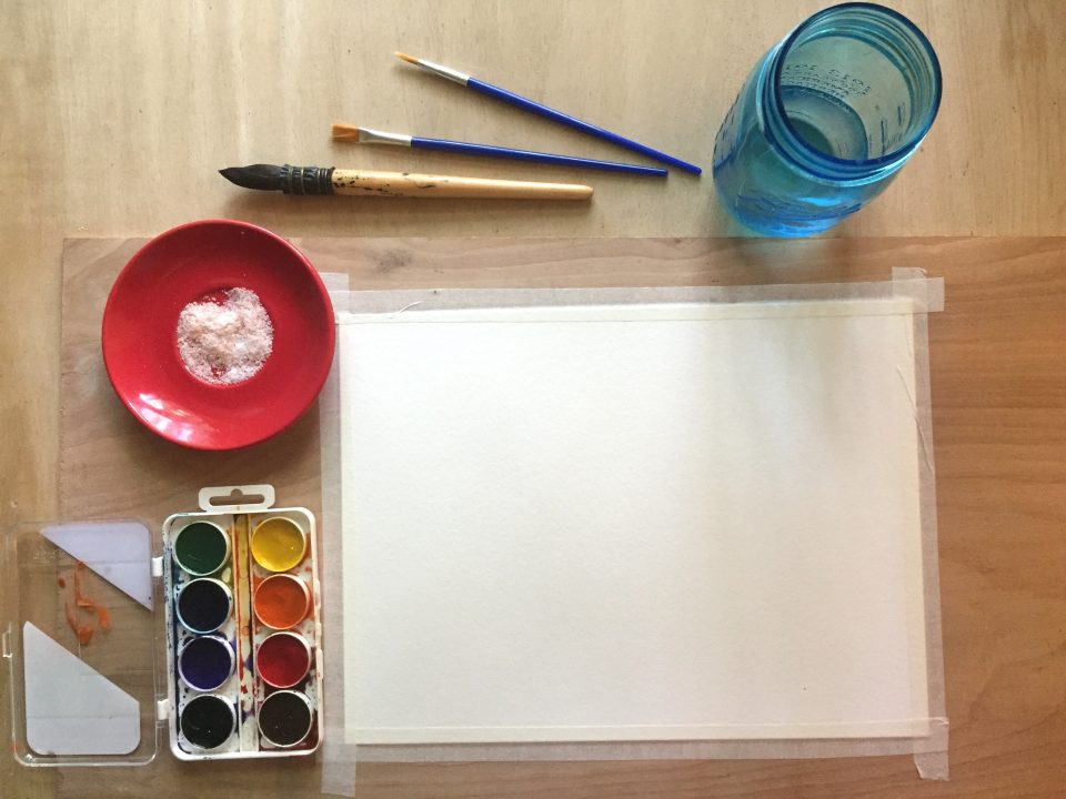 Paper taped to a wood board, watercolors, salt on a red plate, three paint brushes, and a cup of water