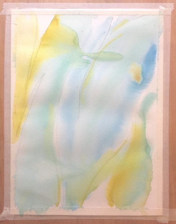 Paper has been painted with loose blue and teal brush strokes of watercolor, with a little bit of yellow in the top left and bottom right.