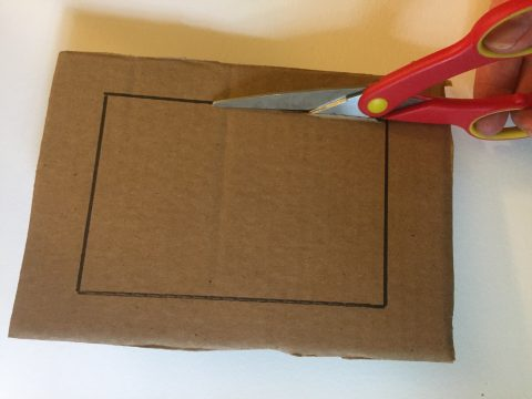 A cardboard rectangle has a smaller rectangle drawn about one inch from the edge and a hand cuts on cuts along the black outline with a pair of scissors.