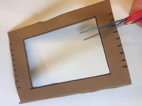 The cardboard rectangle frame has small marks drawn at opposite ends. Scissors cut the short lines.