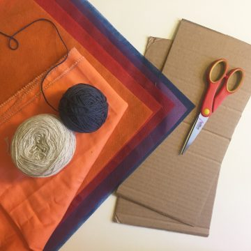 Blue and beige yarn balls on top of tangerine, orange, red, and blue sheer fabric next to two pieces of cardboard and scissors