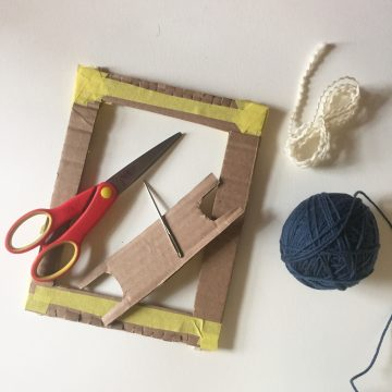 a ball of blue yarn and bundle of wavy white yarn are next to the cardboard loom, cardboard shuttle, scissors, and tapestry needle.