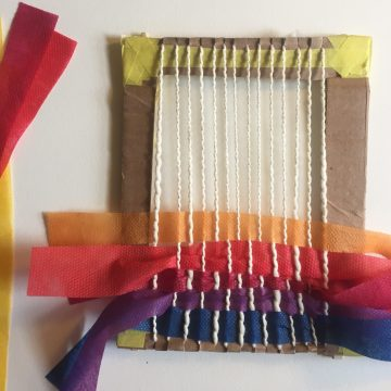 The cardboard loom has white strings running vertically and orange, red, blue, and purple strips of fabric running horizontally, over and under each white string.