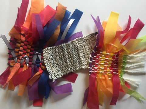 Three finished weavings are displayed. The top weaving is white with red, purple, yellow, and orange. The ends of the weft (horizontal strips of material) are loose and fluffy. The middle weaving is made with smaller yarn. It is mostly beige with a touch of navy. A shimmery yarn has been woven back and forth on the surface of the weaving. The bottom weaving is navy blue with red, orange, purple, and blue. It has a silver ribbon woven through the left side.
