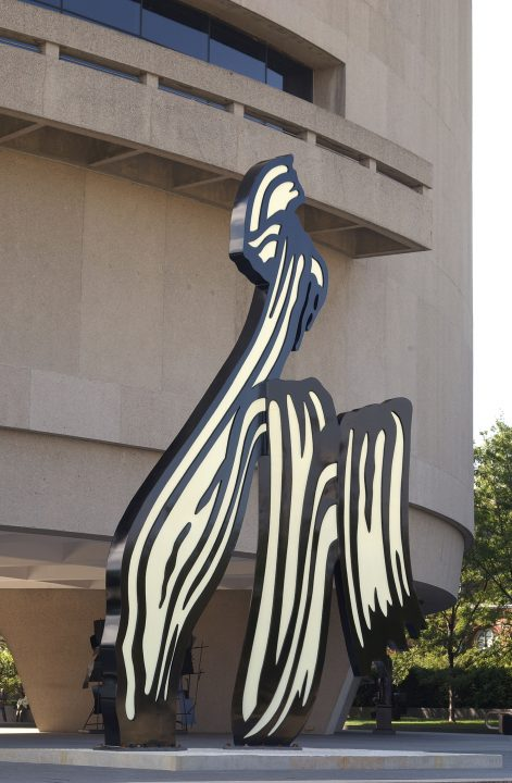 A large sculpture forming an M-like shape in front of one curved side of the Hirshhorn Museum. The sculpture is painted white with a black outline and curvy lines within.
