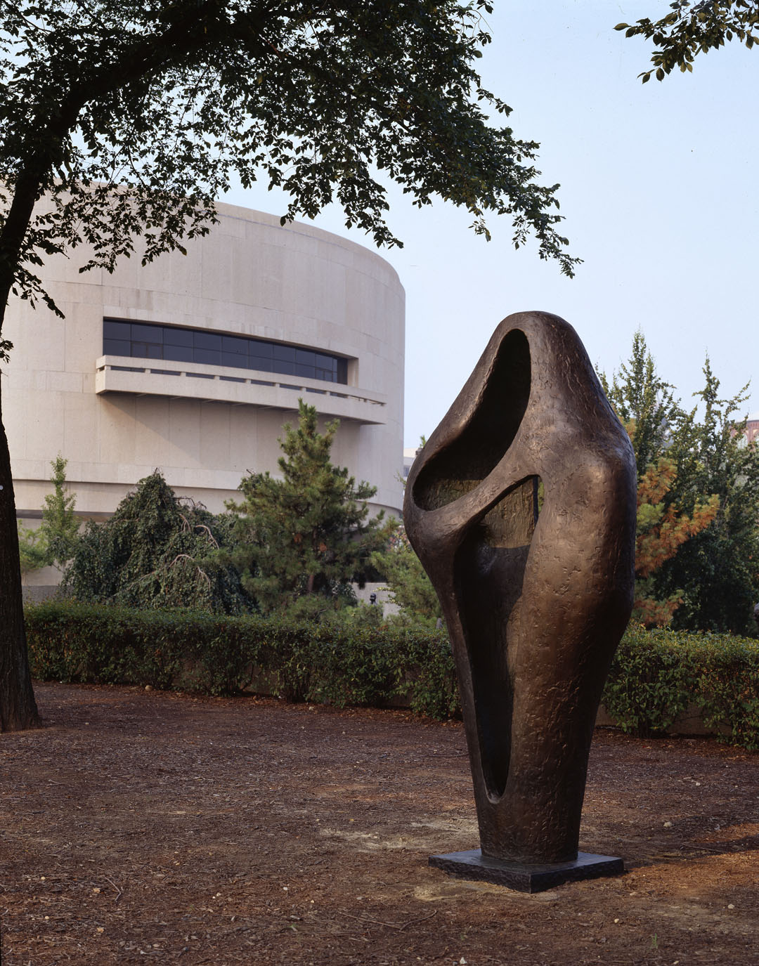 A bronze sculpture is in the photo foreground. A line of bushes, trees and the round shape of the Hirshhorn Museum are in the background.
