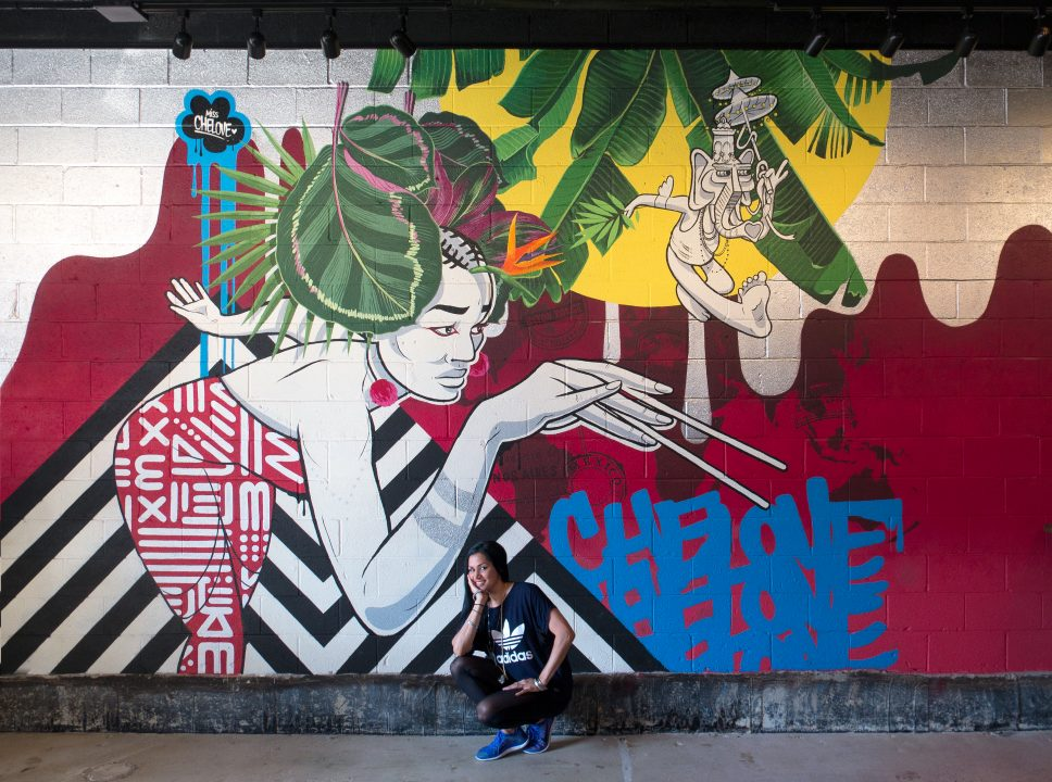 MISS CHELOVE crouches in front of a large wall mural