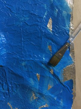 A paint brush rests on a rectangular piece of aluminum foil. The foil is mostly painted bright blue; a few sections of bare foil are exposed.