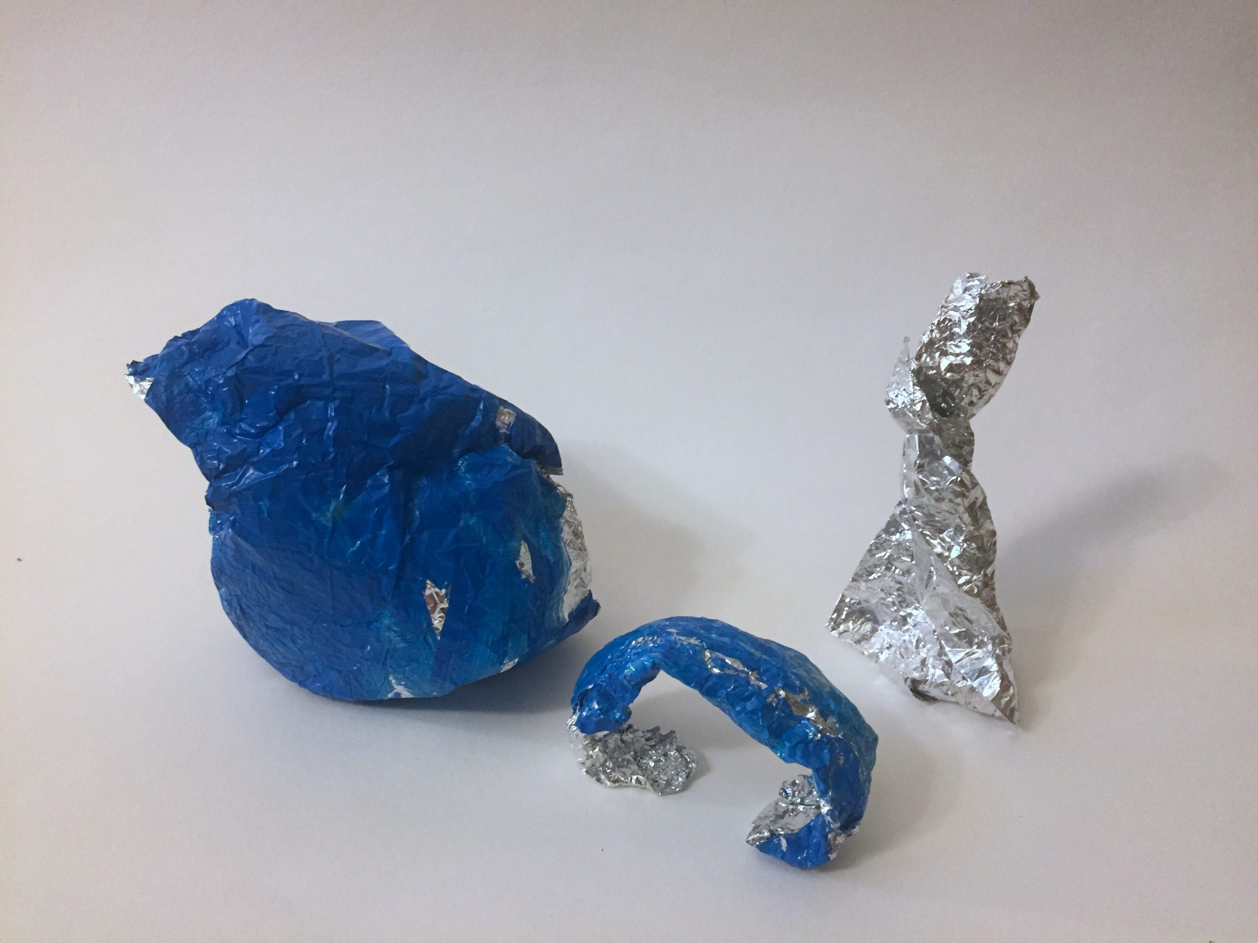 Three aluminum foil sculptures in a row. From left to right: a blue bird-like shape, a blue arch, and an unpainted triangle with a twisted top.