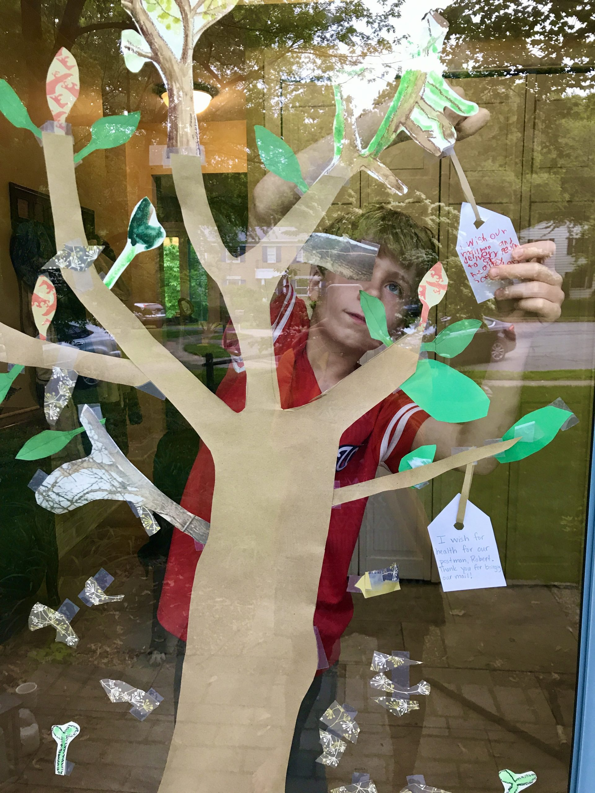 Exterior view of a paper tree with green paper leaves taped to a window, a boy reaches to hang a white tag on one branch