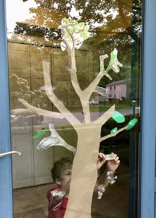 Exterior view of a paper tree with green paper leaves taped on a window, a boy reaches to add to the tree