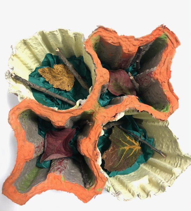 a structure with four cardboard inserts holds several leaves. Each structure is decorated in orange, yellow, and green colors.