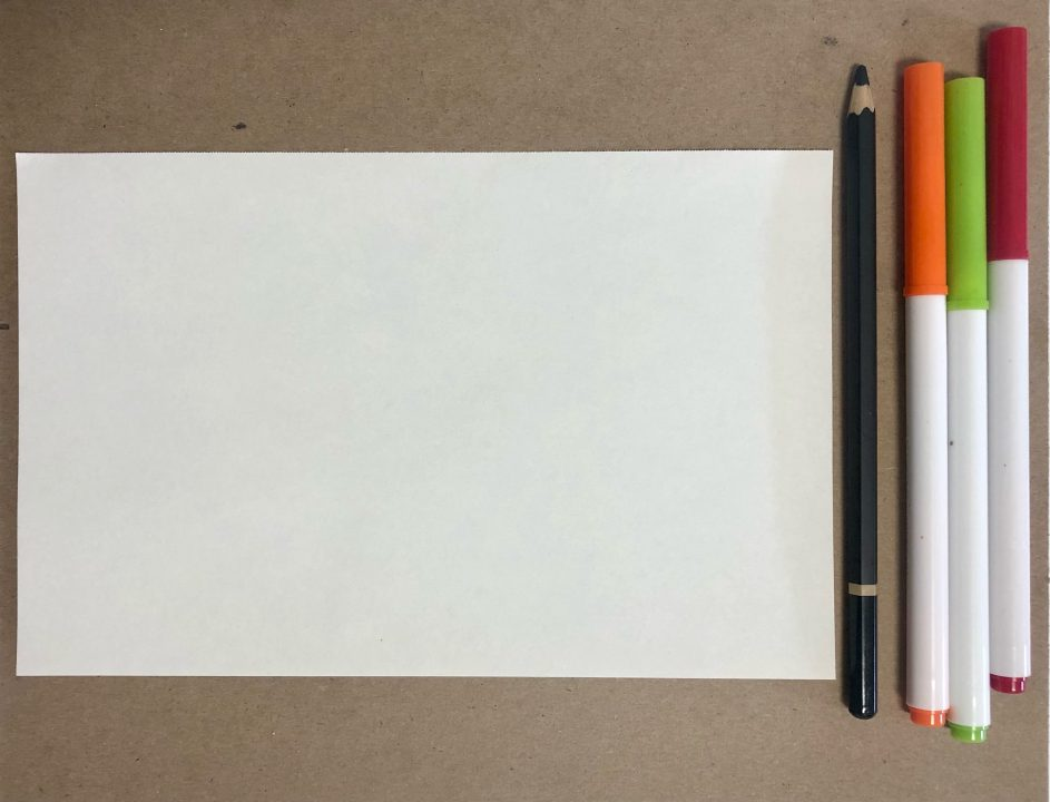 A piece of paper rests on a wood table. A pencil and three markers sit beside the paper.
