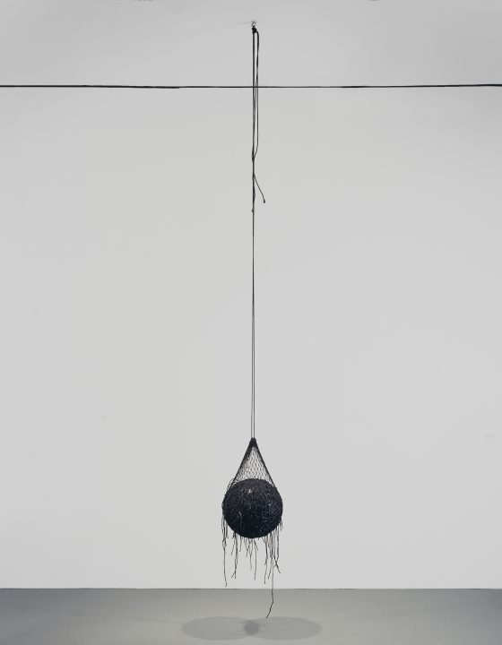 A black ball held inside a black net is suspended from the ceiling in an empty room with white walls.