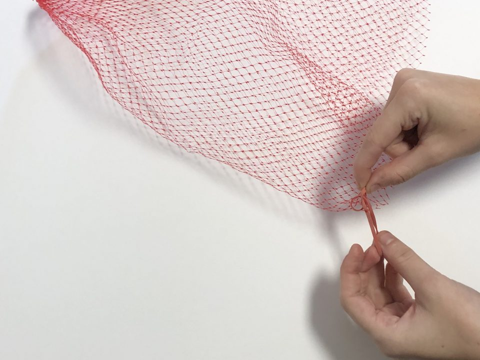 A hand ties a rubber band between the webbing of a red produce net.