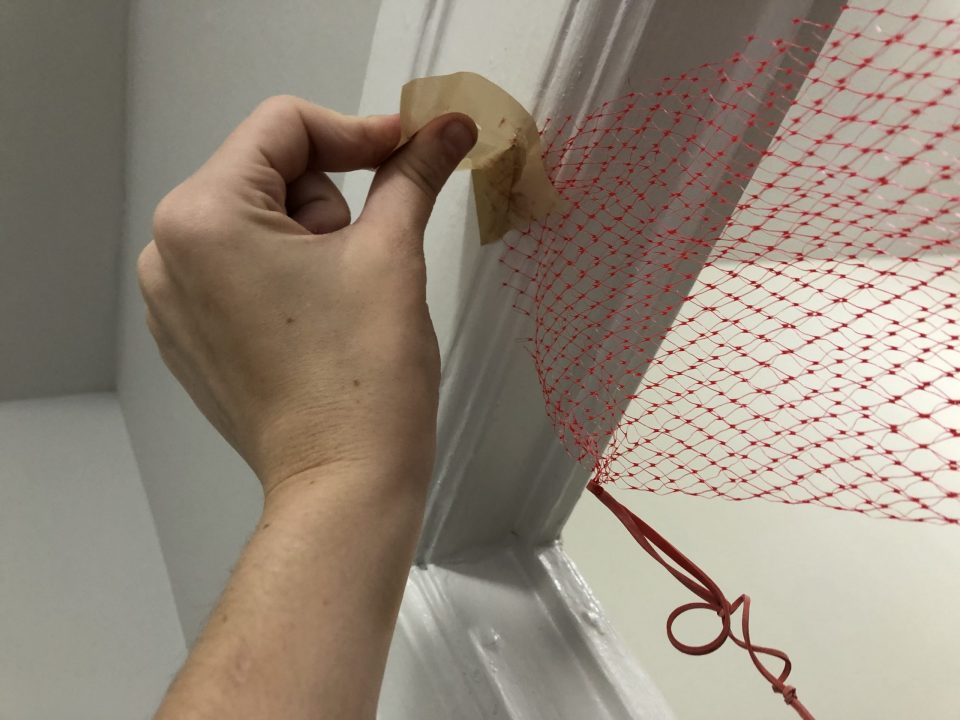 A hand affixes a red net to a door frame with a piece of masking tape.