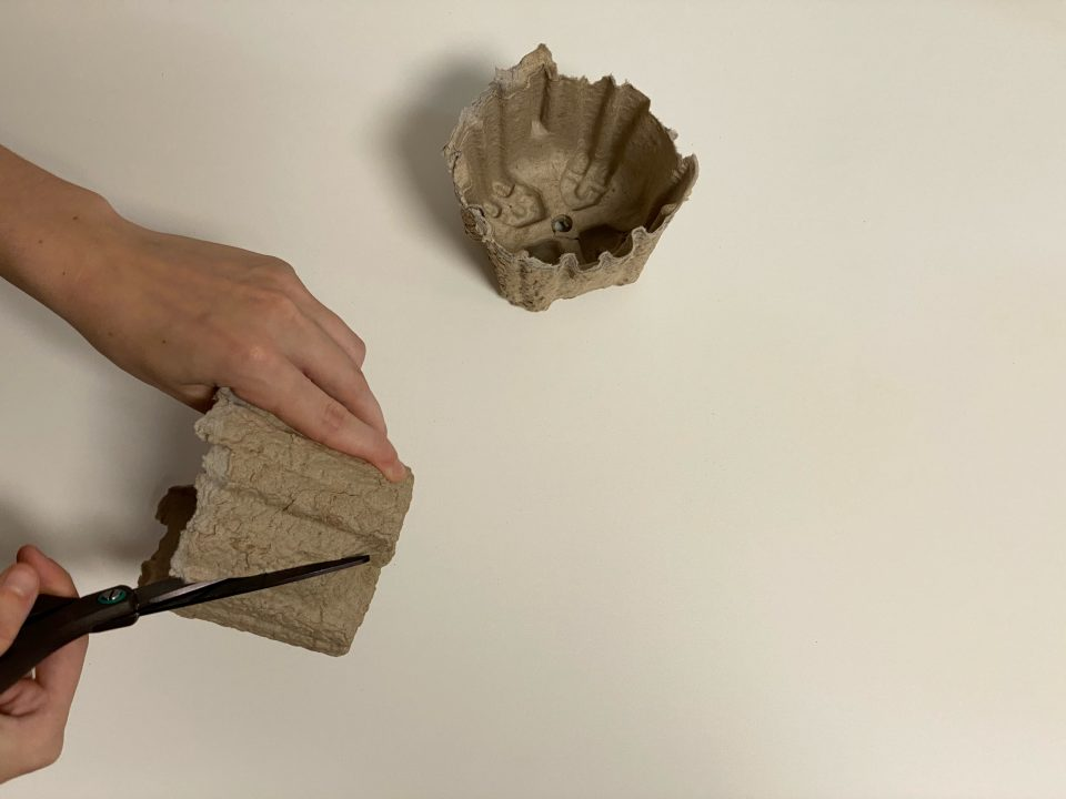 hand holds a circular cardboard insert while scissors cut through it.