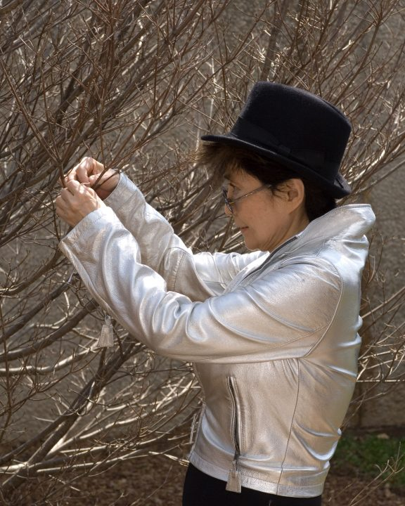 The artist in profile wearing a black hat and silver jacket hangs a tag on a bare tree