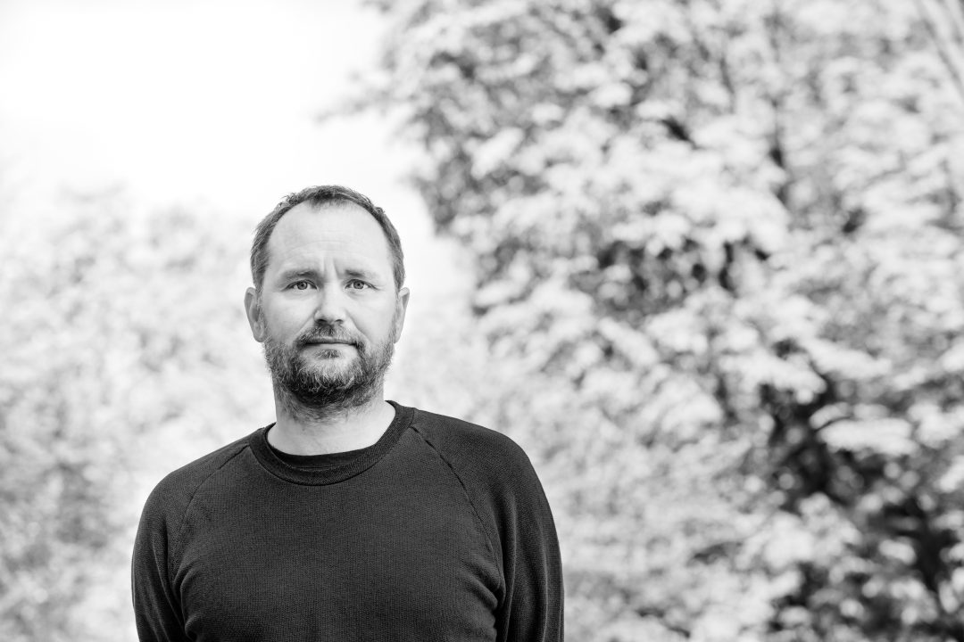 Black and White headshot of Tomás Saraceno standing in front of foliage