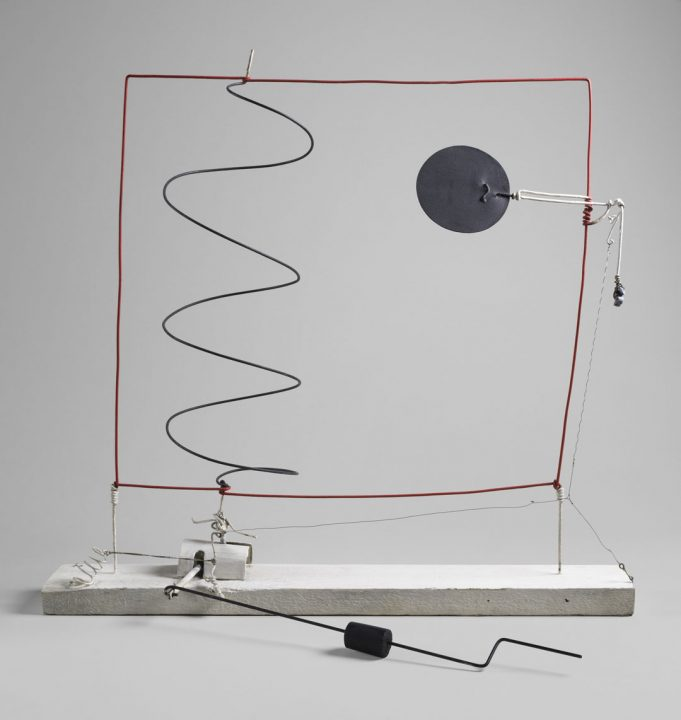 A wood base supports a wire sculpture. The wire is composed of a red outer square with a black spiral in the left-center. A metal motorized disc is suspended in the square's upper-right.