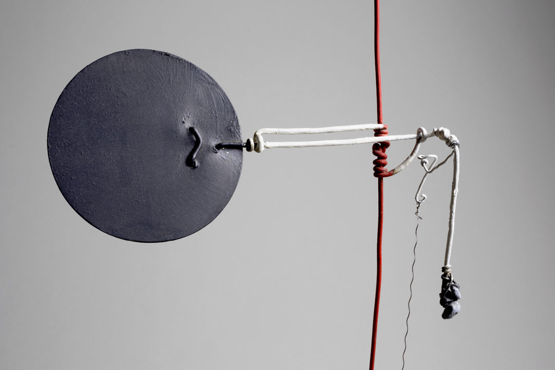 A black metal disc extends from a vertical red wire. A wire lever extends outward, which can be pulled to operate the disc.