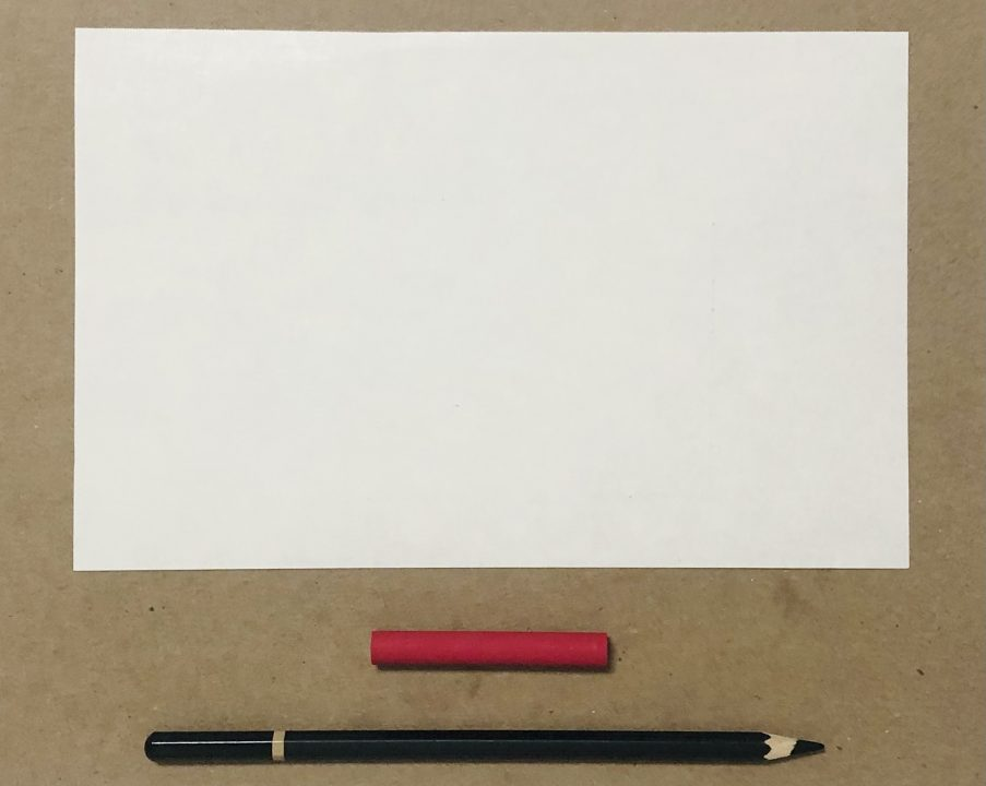 An arrangement of white paper, red crayon, and black pencil.