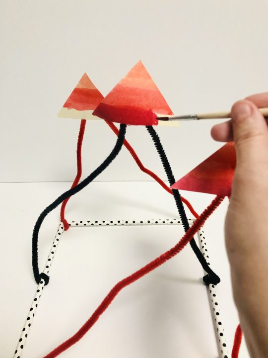 A hand holding a paint brush finishes a line of dark red across the bottom of a triangle. The triangle is suspended in the air by pipe cleaners.