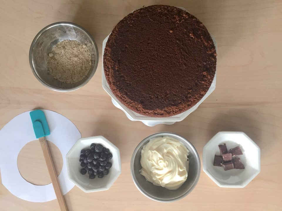 A baked chocolate cake, frosting, chocolate, blueberries, a spatula, cut-out template, and ground almonds displayed on a table.