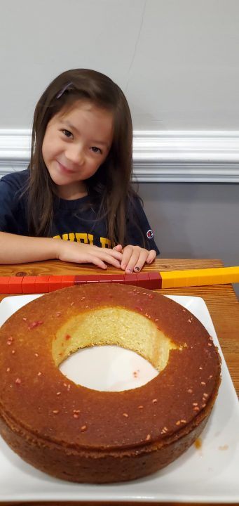Bundt cake with hole cut out in front of a girl smiling
