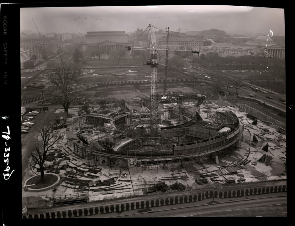 Black and white image. The beginning of construction of the Hirshhorn Museum. A crane is in the center of the building's forming circle.