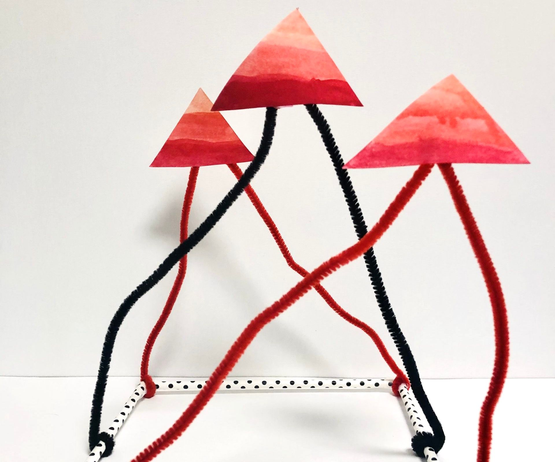 Red, black, and white structure. The square base is made from white polka-dot tubes. Pipe cleaners extend upward displaying three red triangles.