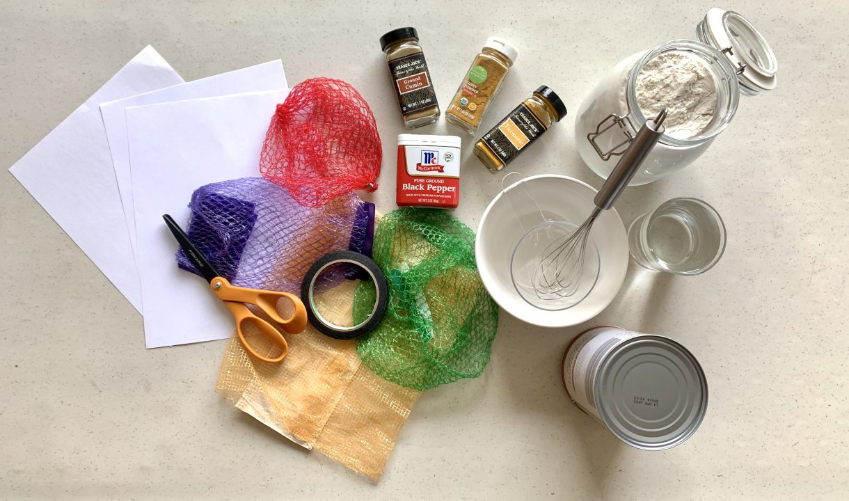An arrangement of paper, scissors, tape, produce nets, spices, water and flour.