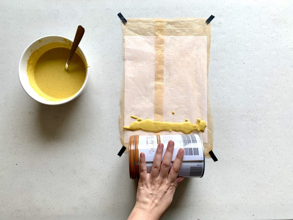 A paper covered with a net is taped to a table. A hand holds a tin can and prepares to roll the can over a line of yellow paint that's drizzled atop the net.