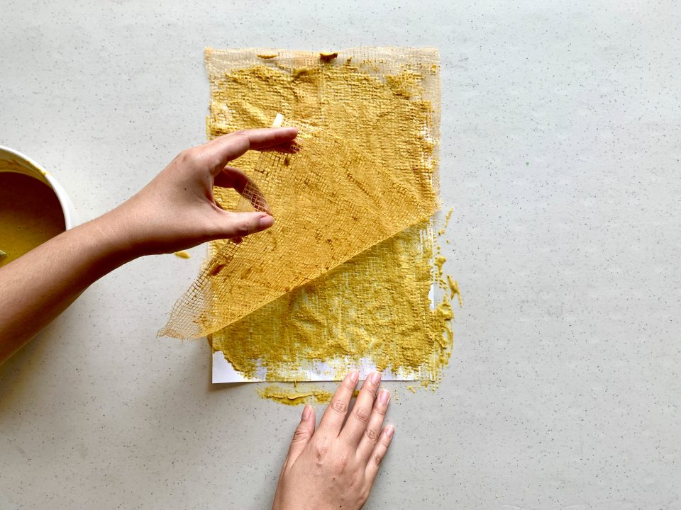 A hand slowly removes a produce net from a bright yellow paper.