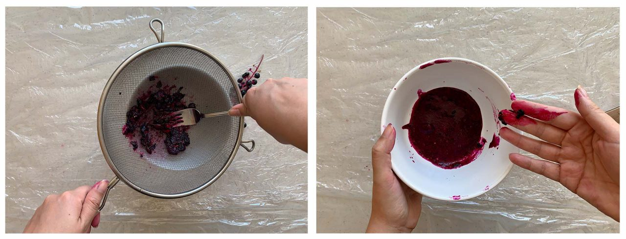 A fork crushes berries inside a colander. On the right, a hand holds a bowl of bright pink berry juice.