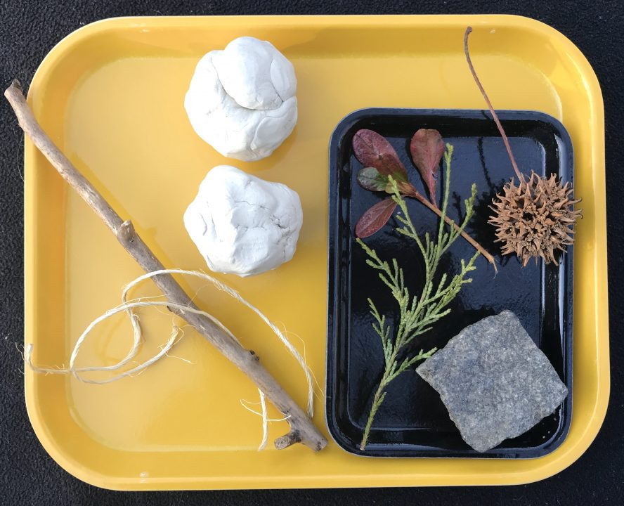 A yellow tray holds two balls of clay, a straight stick, a strand of twine, and a small black tray with leaves, seeds and a diamond-shaped rock.