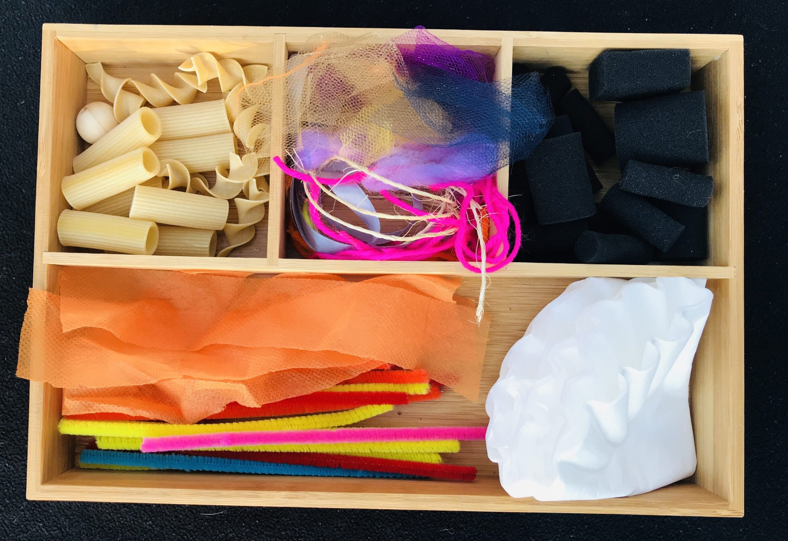 A divided wood tray with four compartments holds dry pasta, string, black foam pieces, pipe cleaners and coffee filters.
