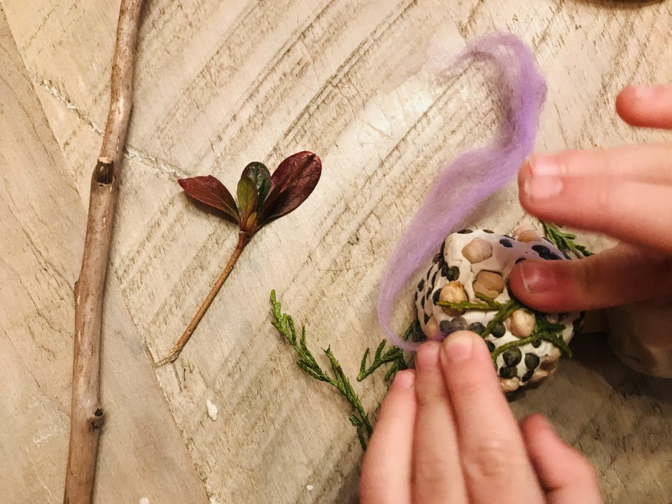 A child's hands press dry beans and green lentils into a ball of clay. A stick, a red leaf, and purple wool are arranged nearby on the wood table.