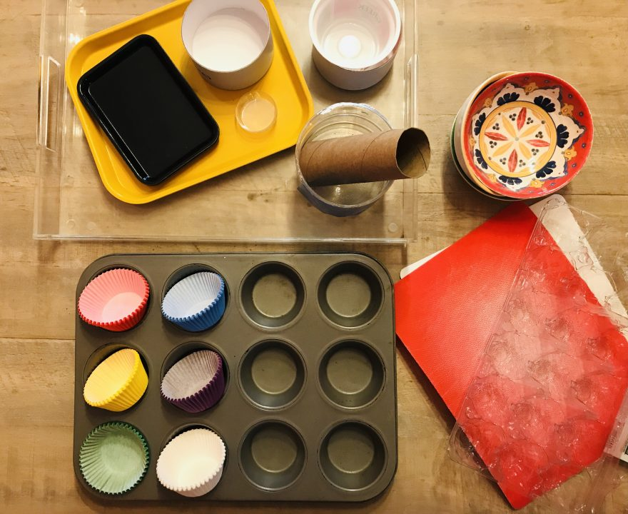 Cooking tray with colorful cupcake liner, bowls,and other knick knacks