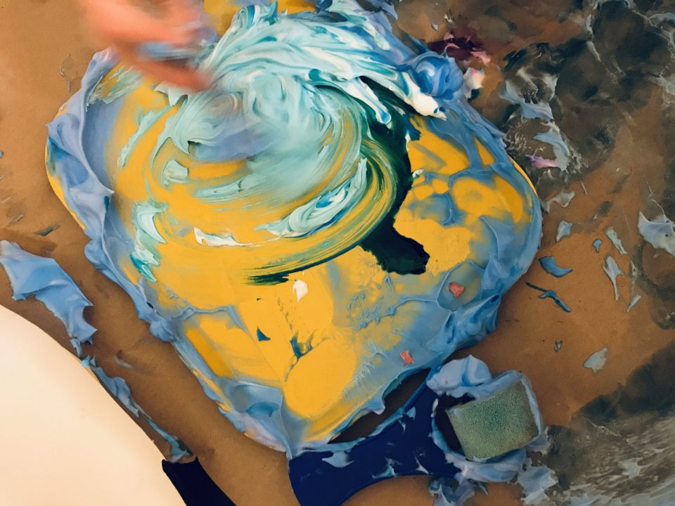 A yellow tray covered in swirls of paint rests on paint-covered brown Kraft paper. In the top left corner, a blurred hand is quickly stirring the paint.