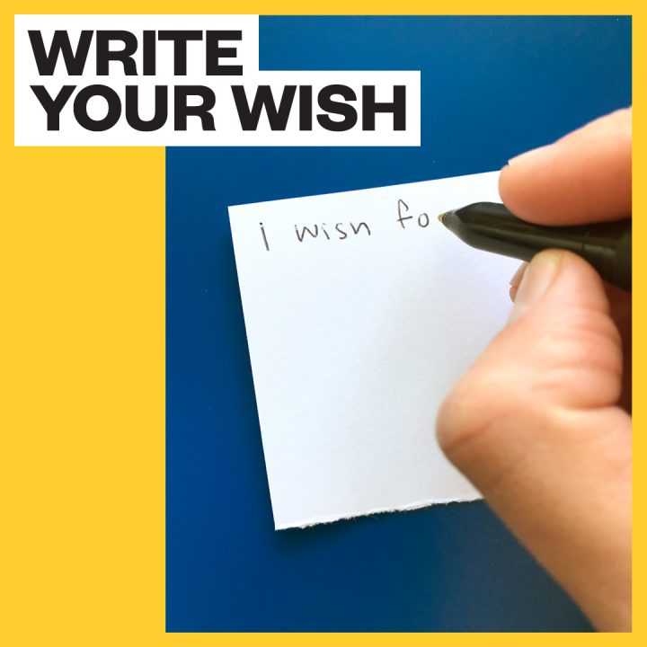 "Text reads ""write your wish"" Hand holding pen is writing on white paper"