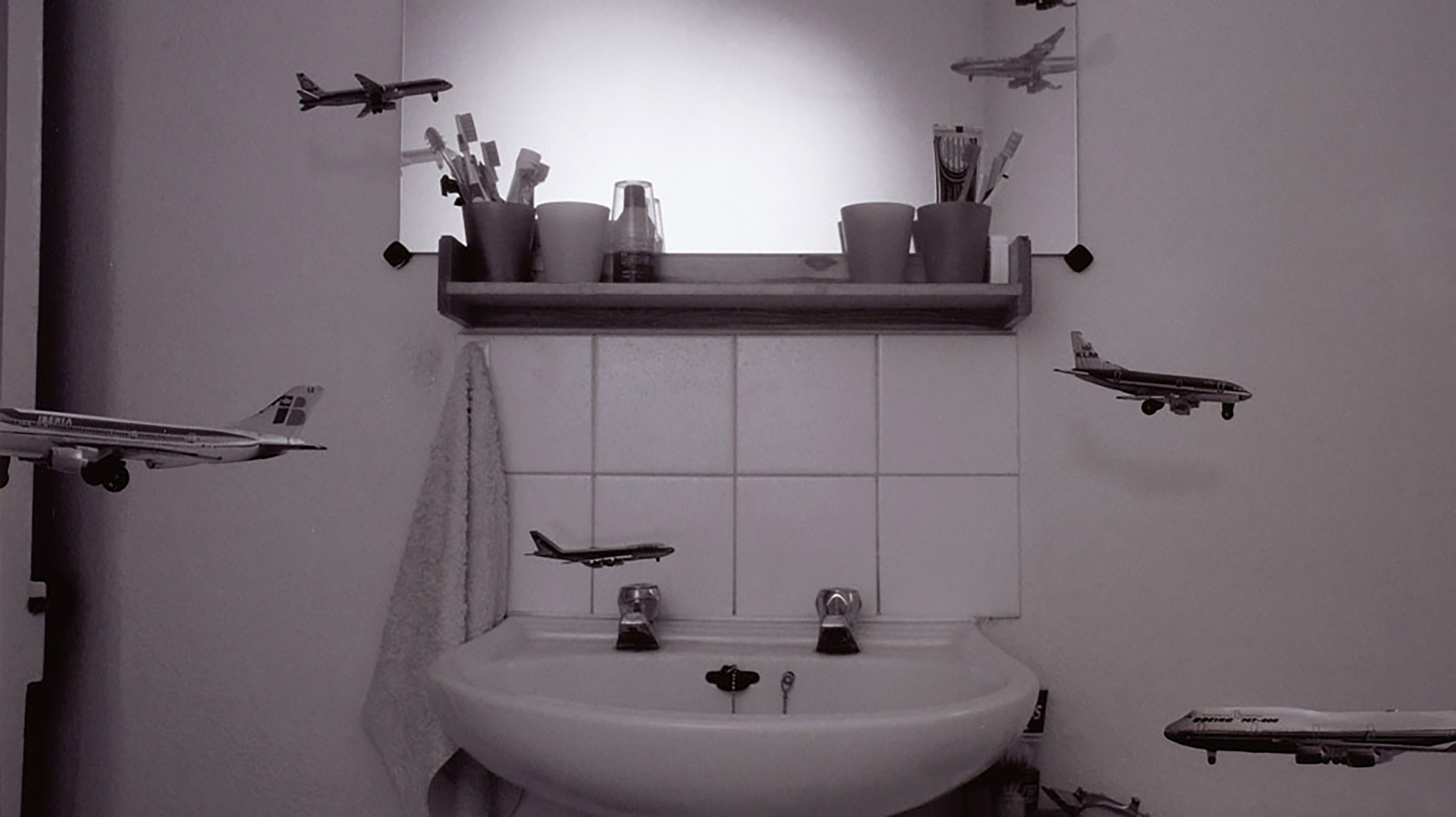 Black and white photo. Small miniature planes flying around in a bathroom.