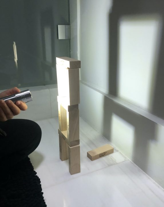 A tower of blocks casts a shadow on a wall. To the left, a hand points a flashlight at the tower. The shadow cast on the wall is much larger than the actual tower.