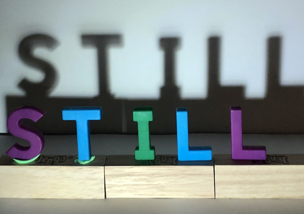 """An arrangement of letter tiles spells the word """"STILL."""" On a wall behind it, the words are enlarged in a shadow."""