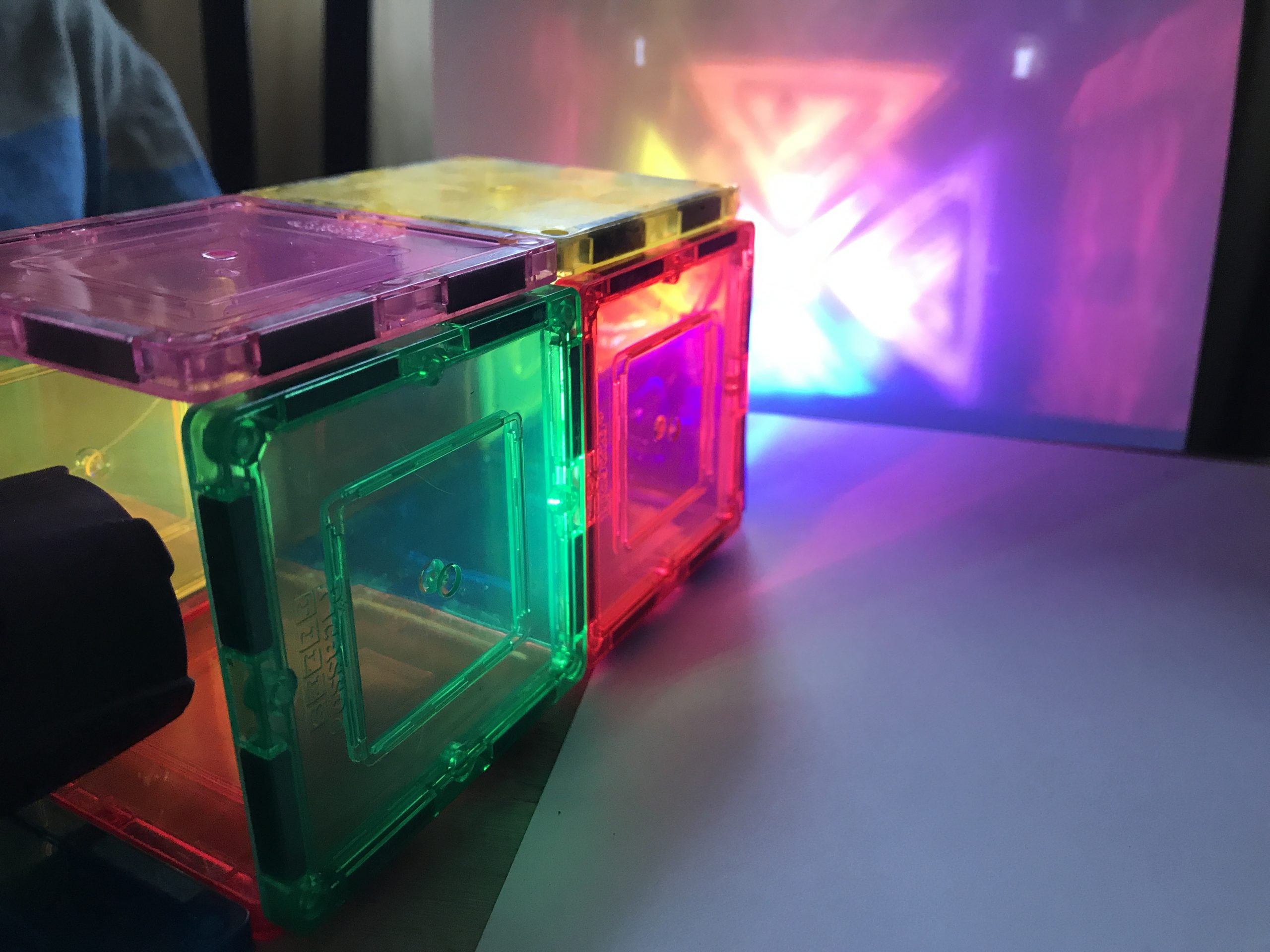 A flashlight shines through the end of a rectangular construction of colorful, translucent blocks, casting a projections of bright triangular shapes against a blank piece of paper.