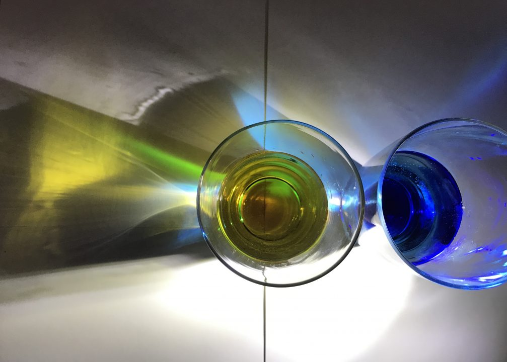 Two clear glasses on a piece of white paper. One glass has blue liquid, the other has yellow. To the left a shadow of the glass is cast, with yellow, blue and green reflections inside.